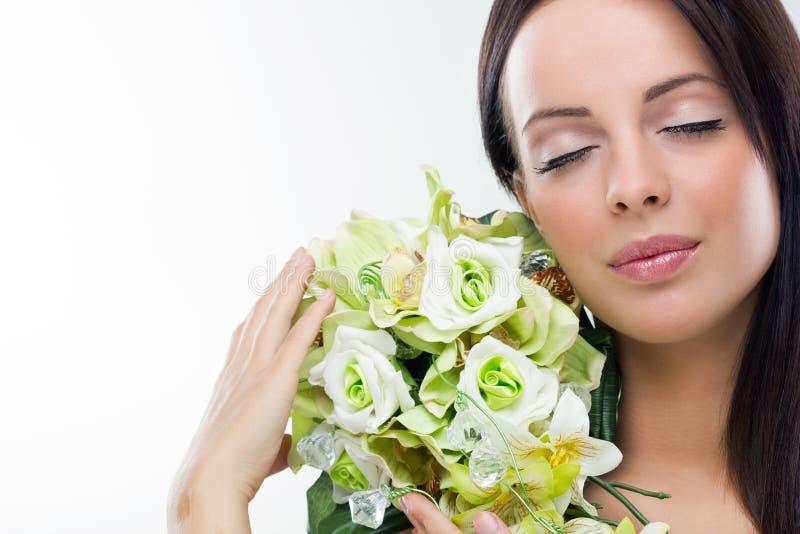 Bella giovane donna che tiene un fiore fotografia stock libera da diritti