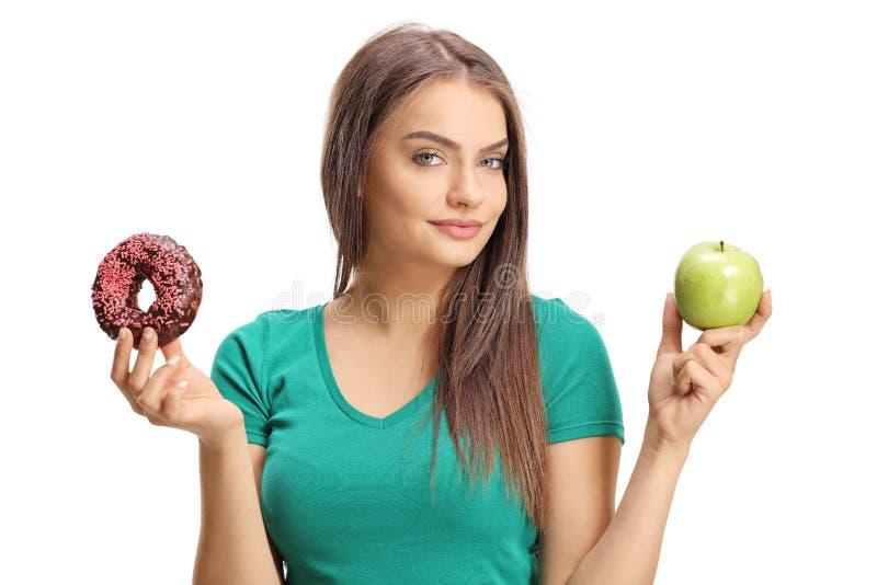 Bella giovane donna che tiene una mela e una ciambella fotografie stock libere da diritti