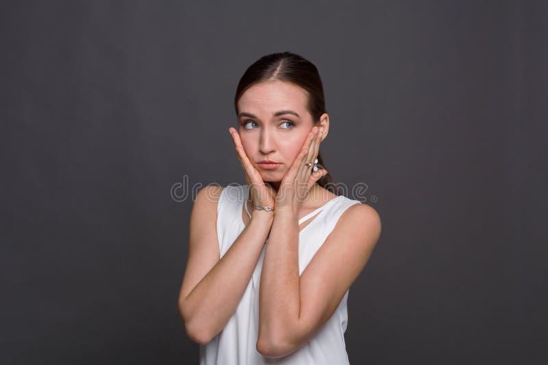Bella giovane donna che tocca il suo fronte immagine stock