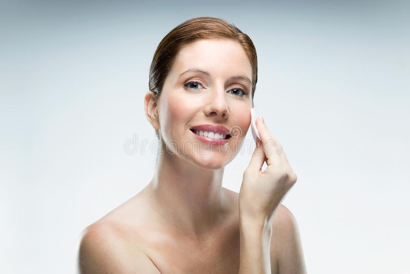 Bella giovane donna che usando i cosmetici sopra fondo bianco immagine stock