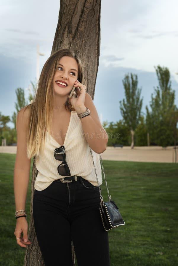 Bella giovane donna che utilizza il suo telefono cellulare nel parco al tramonto fotografia stock libera da diritti