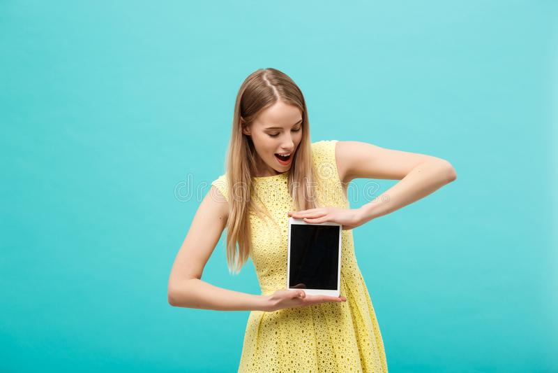 Bella giovane donna colpita emozionante in vestito giallo che confonde o espressione imbarazzata sul fronte mentre ricevendo immagini stock libere da diritti