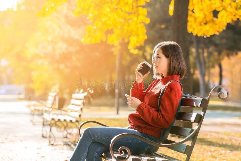 Bella giovane donna con caffè che si siede sul banco di legno nel parco di autunno fotografie stock libere da diritti