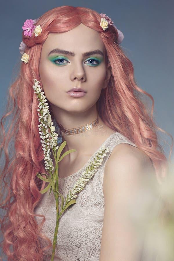 Bella giovane donna con capelli ed i fiori rosa fotografie stock libere da diritti