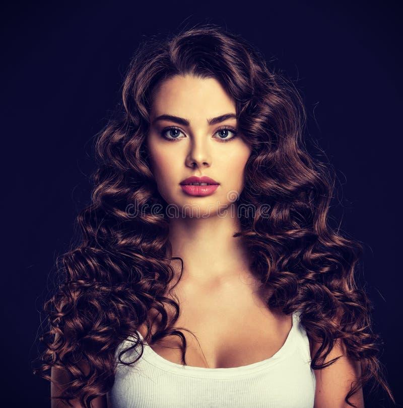 Bella giovane donna con capelli marroni ricci lunghi fotografie stock