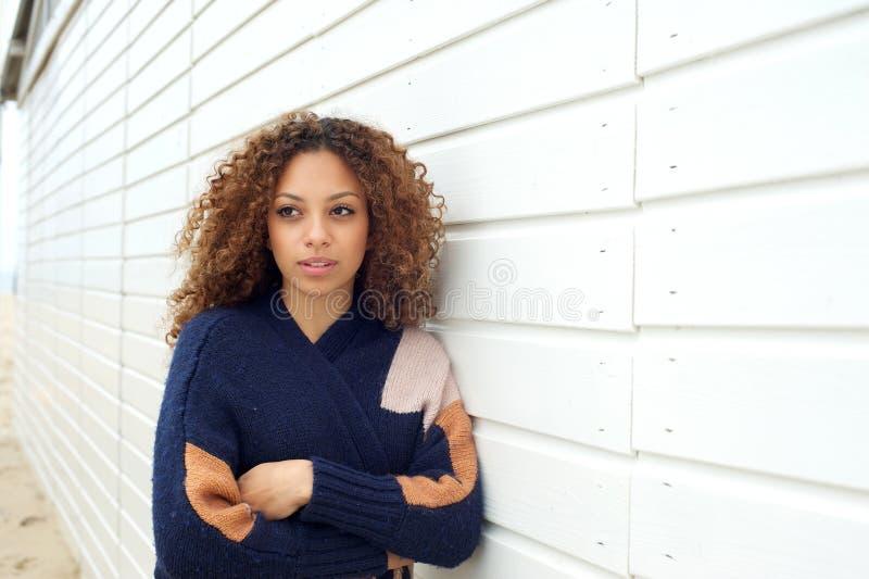 Bella giovane donna con capelli ricci ed il maglione che posano all'aperto fotografia stock