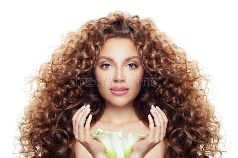 Bella giovane donna con capelli ricci lunghi, chiara pelle ed il fiore del giglio isolati su bianco fotografia stock