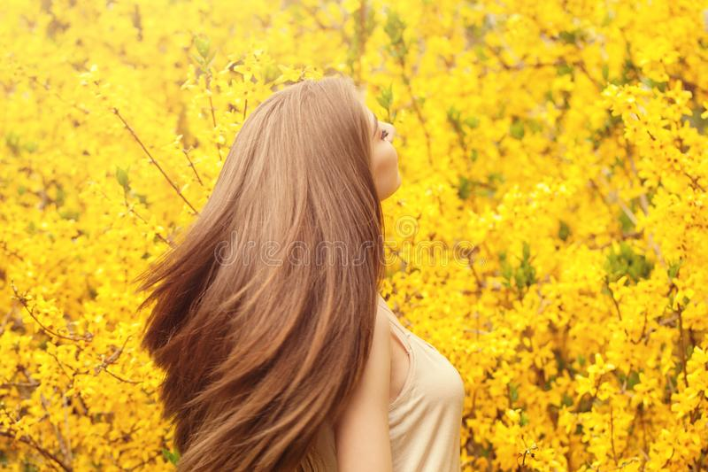Bella giovane donna con capelli sani lunghi contro il fondo giallo dei fiori Ragazza con il ritratto di salto dell'acconciatura fotografia stock