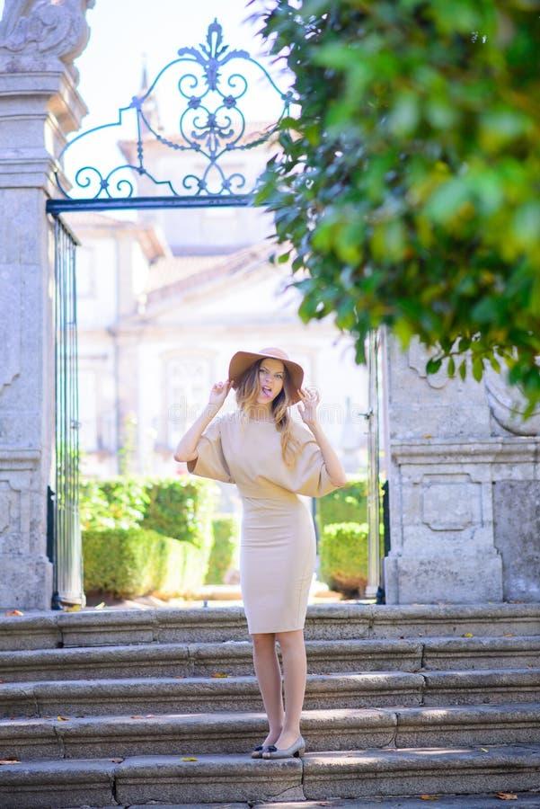 Bella giovane donna con capelli scuri in vestito beige elegante che posa sulle scale immagini stock libere da diritti