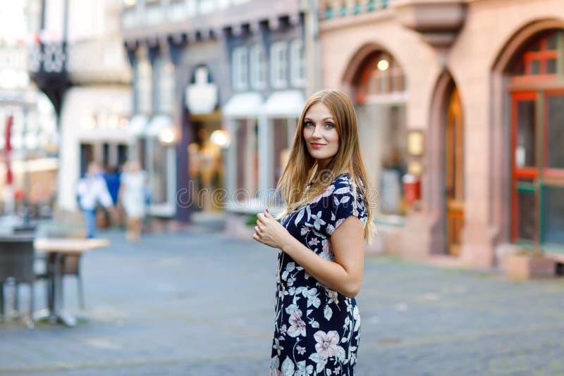 Bella giovane donna con i capelli lunghi in vestito da estate che va a fare una passeggiata nella città tedesca Ragazza felice ch fotografia stock libera da diritti