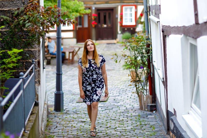 Bella giovane donna con i capelli lunghi in vestito da estate che va a fare una passeggiata nella città tedesca Ragazza felice ch immagine stock libera da diritti