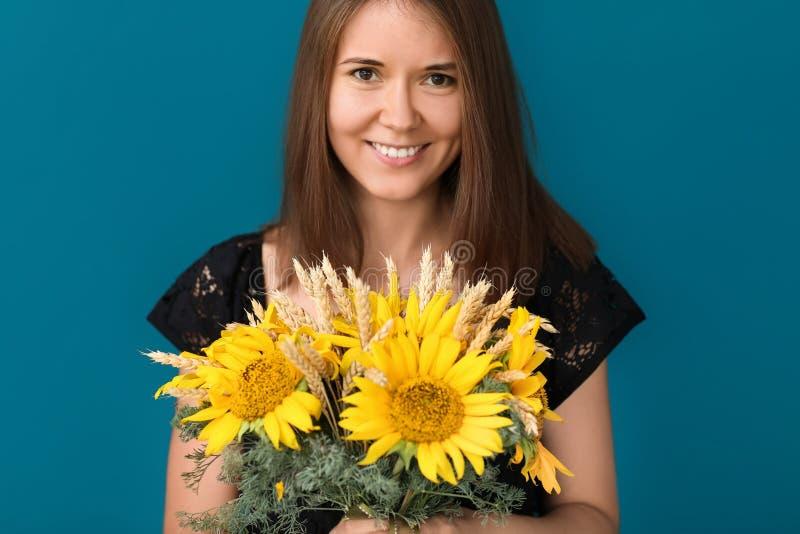 Bella giovane donna con i girasoli sul fondo di colore fotografia stock libera da diritti