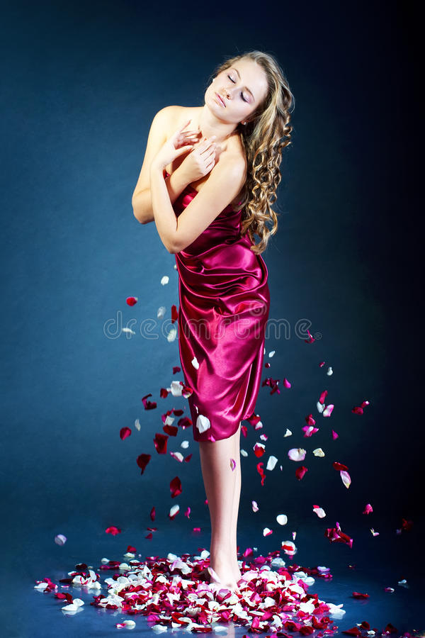Bella giovane donna con i petali di rosa del fiore immagine stock