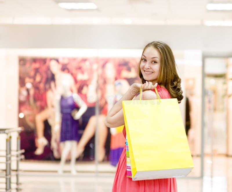 Bella giovane donna con i sacchetti della spesa in un supermercato fotografia stock libera da diritti