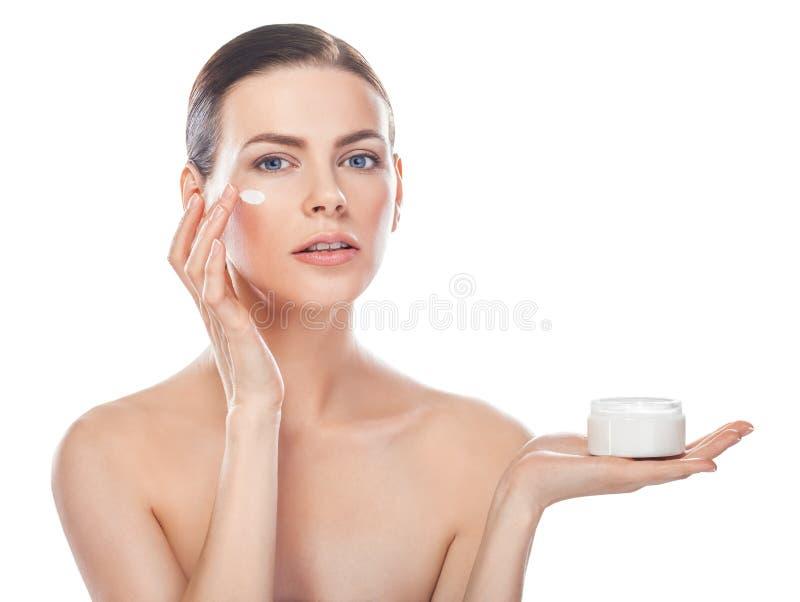 Bella giovane donna con il barattolo di crema crema e cosmetica sulla a fotografia stock libera da diritti