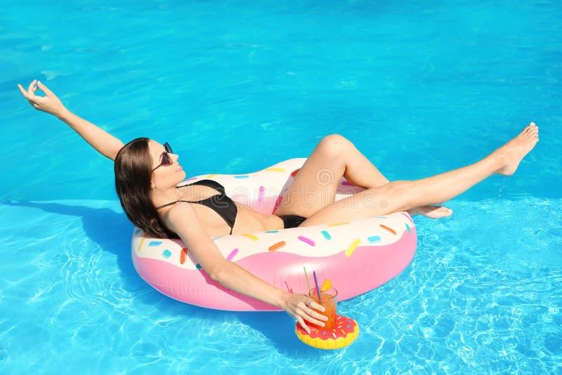 Bella giovane donna con il bikini d'uso del cocktail sull'anello gonfiabile fotografie stock libere da diritti