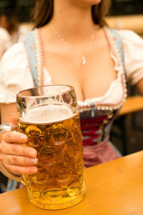 Bella giovane donna con il boccale in pietra della birra a Monaco di Baviera Oktoberfest fotografie stock
