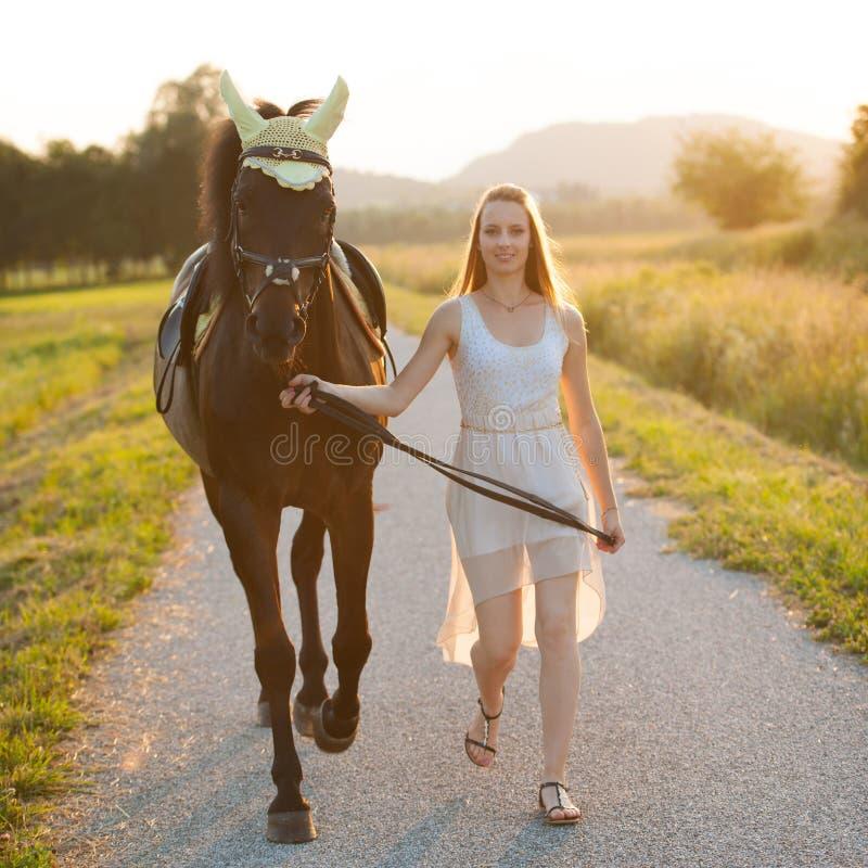 Bella giovane donna con il cavallo all'aperto su una passeggiata in natura fotografia stock libera da diritti