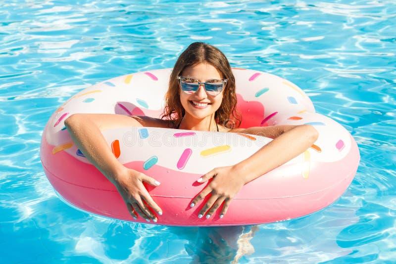 Bella giovane donna con il cerchio rosa che si rilassa nella piscina blu fotografia stock
