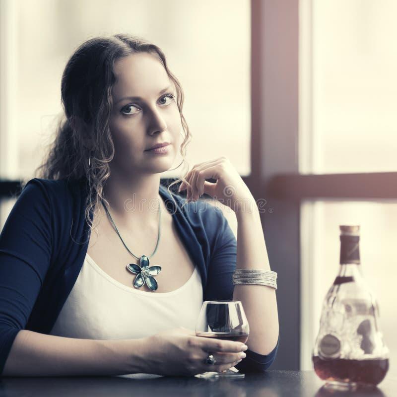 Bella giovane donna con il cognac al ristorante fotografia stock