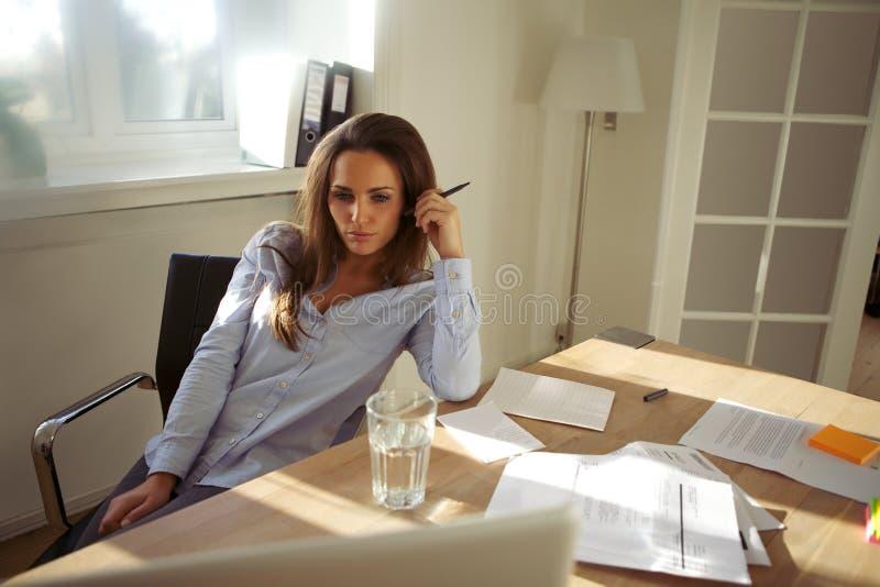 Bella giovane donna con il computer portatile che funziona dalla casa immagine stock libera da diritti