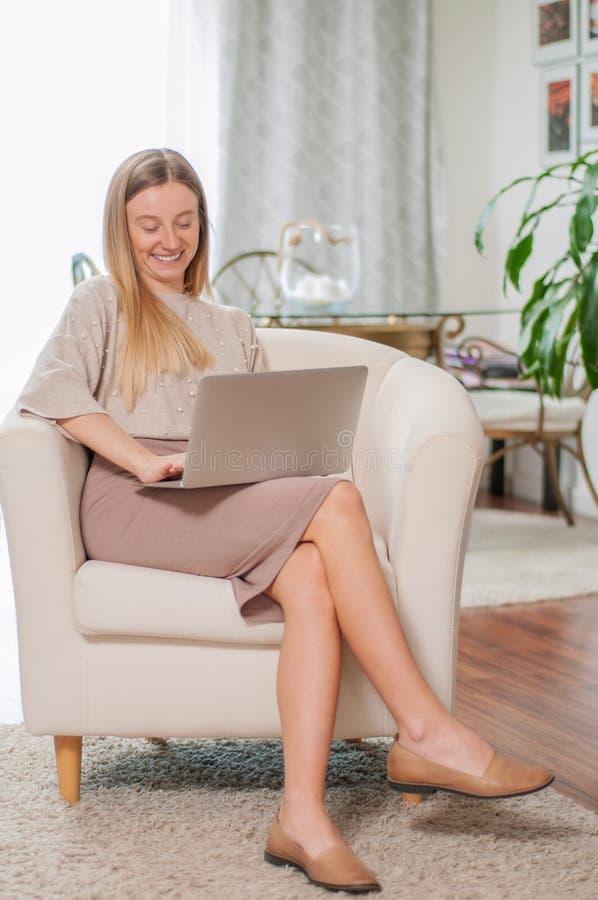 Bella giovane donna con il computer portatile che si siede nella sedia comoda a casa fotografia stock