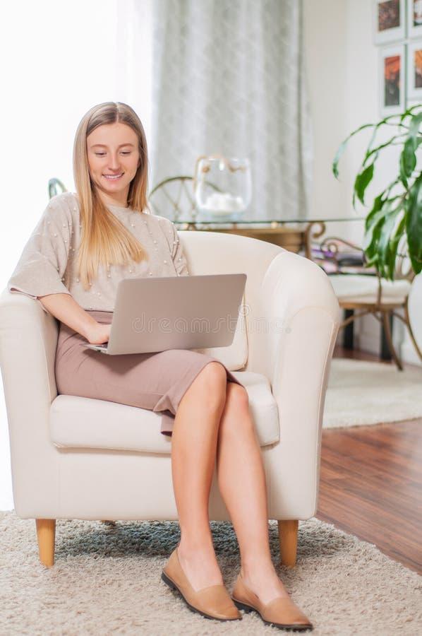 Bella giovane donna con il computer portatile che si siede nella sedia comoda a casa fotografia stock libera da diritti