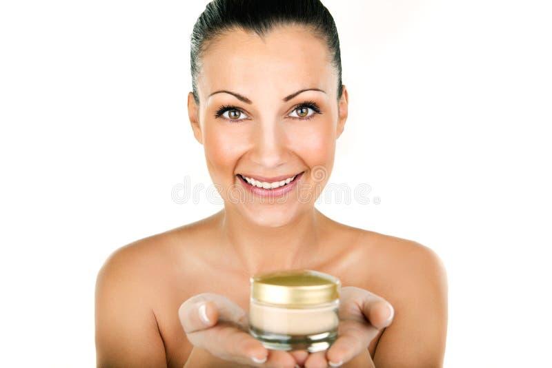 Bella giovane donna con il fiore su una crema del cosmetico e dei capelli fotografia stock