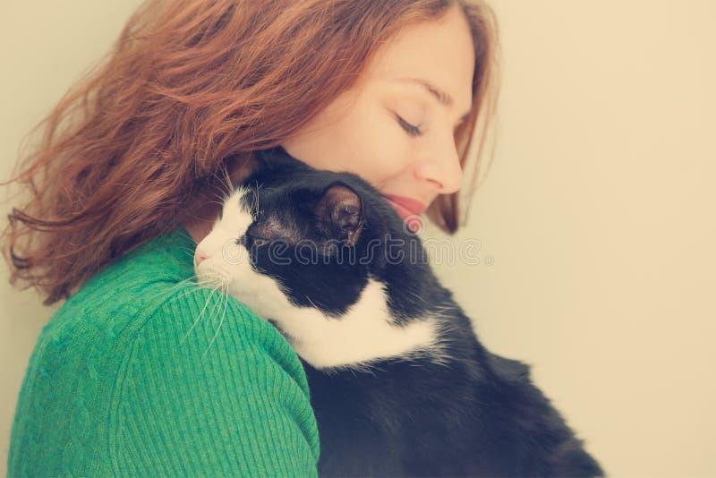 Bella giovane donna con il gatto in bianco e nero fotografie stock libere da diritti