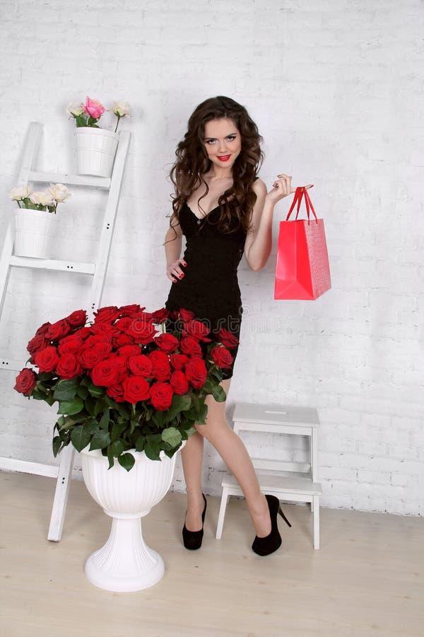 Bella giovane donna con il mazzo delle rose rosse e del contenitore di regalo, Va immagine stock