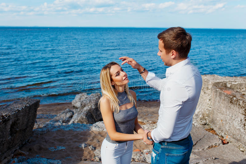 Bella giovane donna con il suo ragazzo sulla spiaggia immagine stock