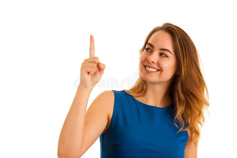Bella giovane donna con il vestito blu che indica nello spazio della copia fotografia stock libera da diritti
