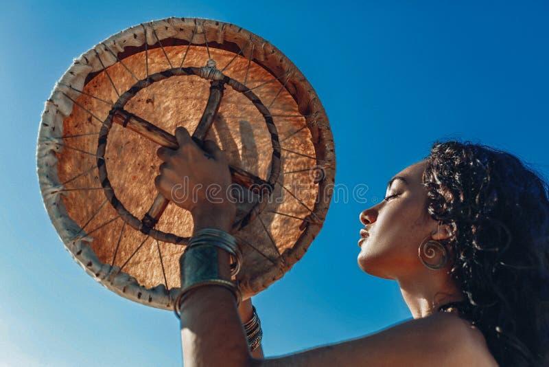Bella giovane donna con l'aria aperta ed il gioco del tamburo dello sciamano della musica etnica immagini stock