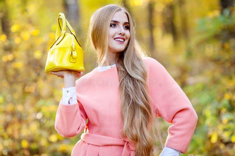 Bella giovane donna con la borsa alla moda gialla in mani sulla natura di autunno immagine stock libera da diritti