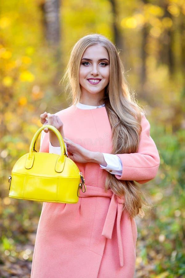 Bella giovane donna con la borsa alla moda gialla in mani sulla natura di autunno immagini stock