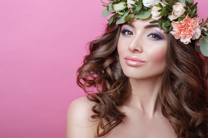 Bella giovane donna con la corona del fiore e dei capelli ricci sulla sua testa sulla ragazza rosa di bellezza del fondo con l'ac fotografia stock libera da diritti