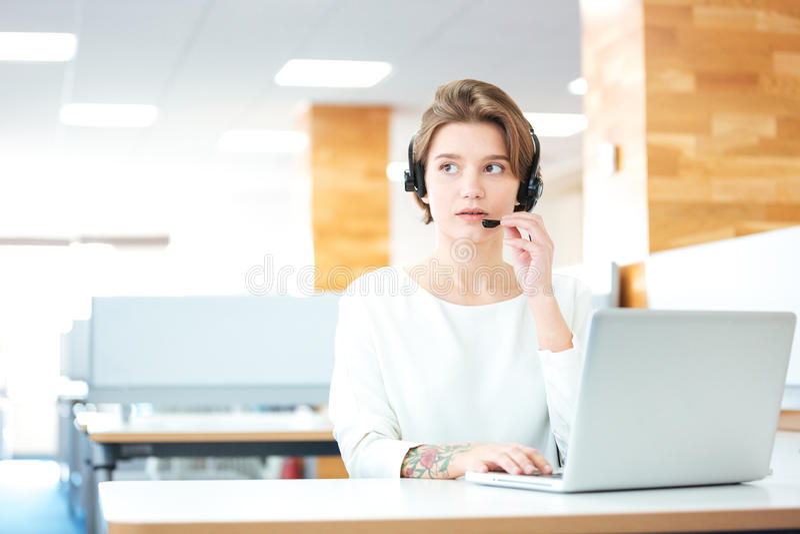 Bella giovane donna con la cuffia avricolare che funziona nella call center immagine stock libera da diritti