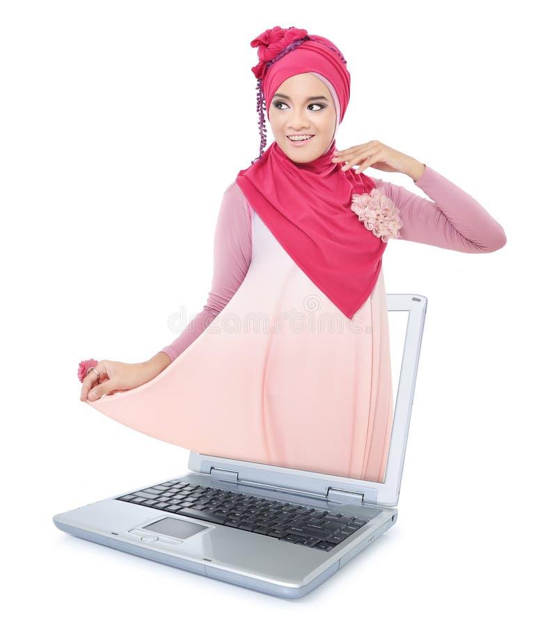 Bella giovane donna con la sciarpa rosa dal computer portatile fotografie stock libere da diritti