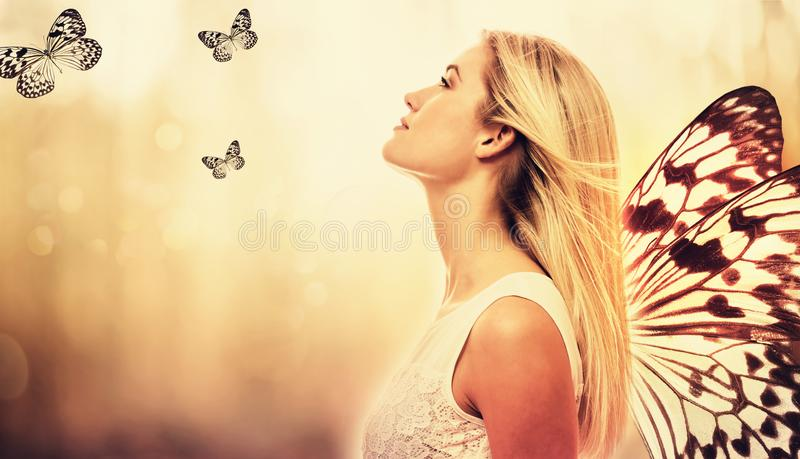 Bella giovane donna con le ali della farfalla fotografia stock