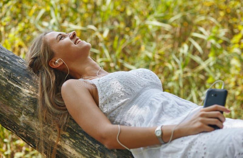 Bella giovane donna con le cuffie che si rilassano sulla natura fotografia stock libera da diritti