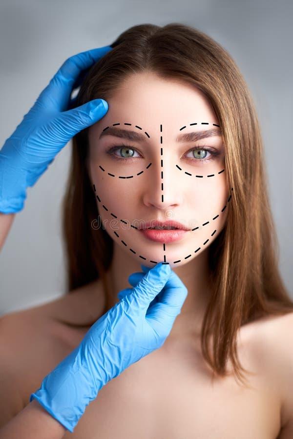 Bella giovane donna con le righe di perforazione sul suo fronte prima del funzionamento della chirurgia plastica E fotografia stock libera da diritti