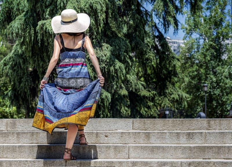Bella giovane donna con le stelle rampicanti di un cappello di paglia fotografia stock