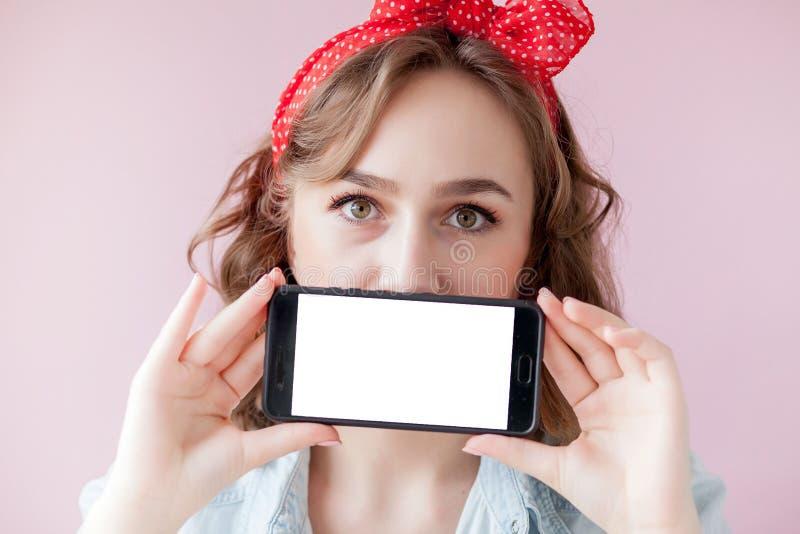 Bella giovane donna con trucco di pin-up e acconciatura sopra fondo rosa con il telefono cellulare con lo spazio della copia fotografia stock