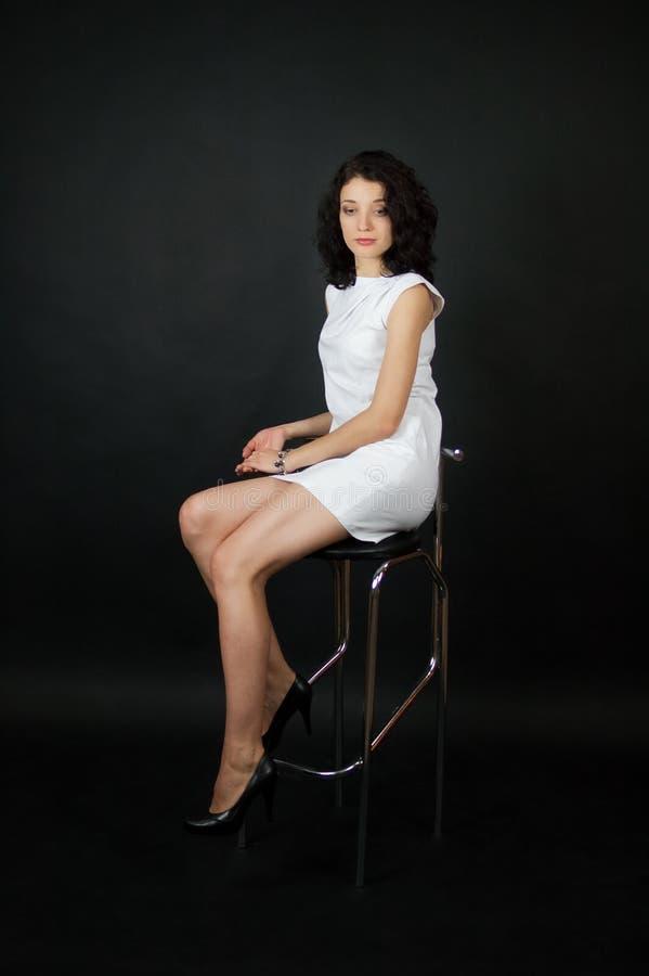 Bella giovane donna con trucco di sera in breve vestito bianco che si siede sulla sedia della barra in studio sopra fondo nero fotografia stock