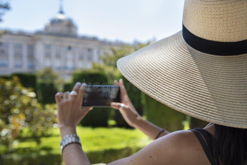 Bella giovane donna con un cappello di paglia che prende una fotografia con il cellulare fotografie stock