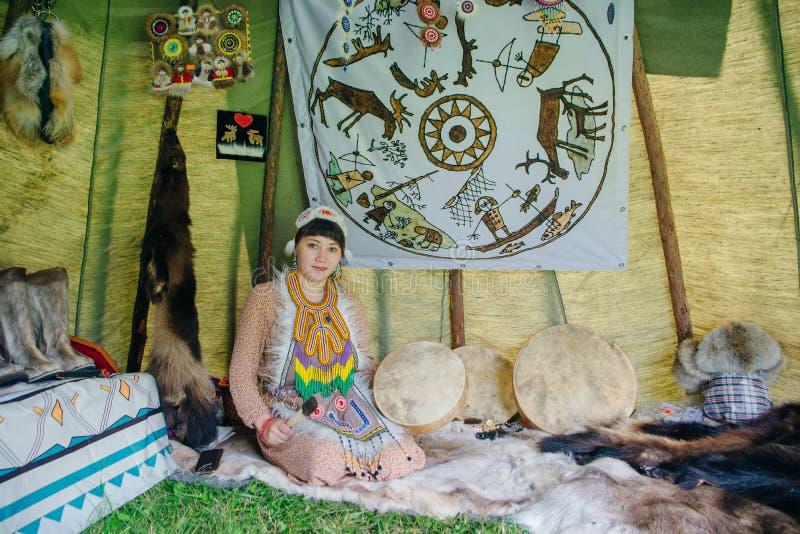 bella giovane donna con un tamburo dello sciamano in un wigwam che gioca musica etnica immagini stock libere da diritti