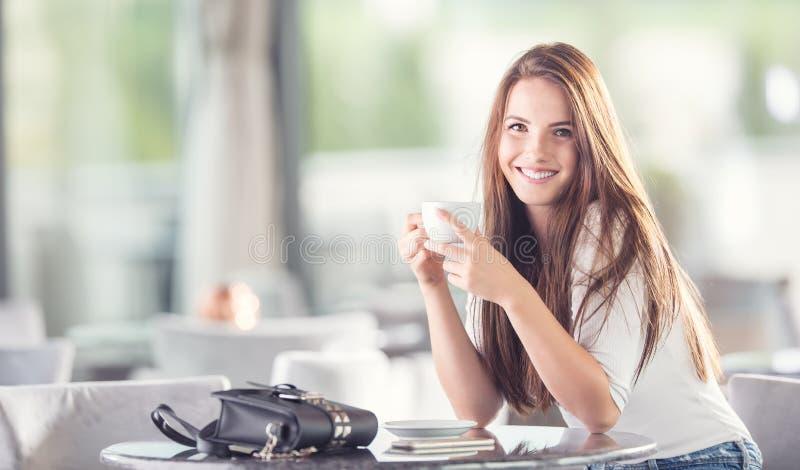 Bella giovane donna con una tazza di caffè o tè nel caffè fotografie stock