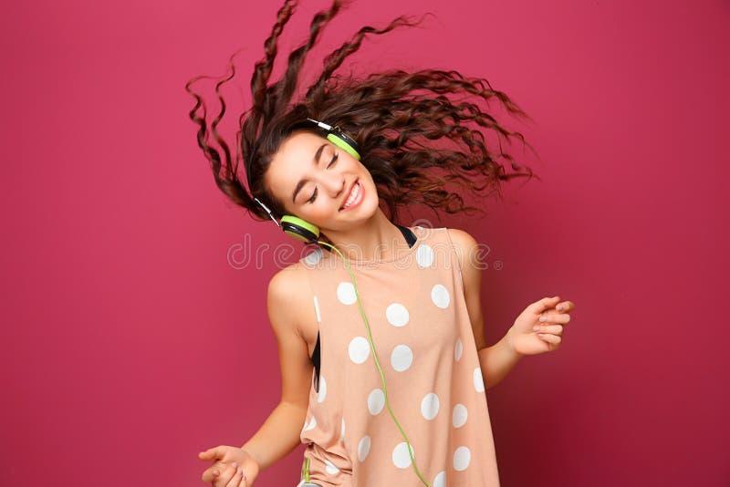 Bella giovane donna in cuffie che ascolta la musica fotografia stock libera da diritti