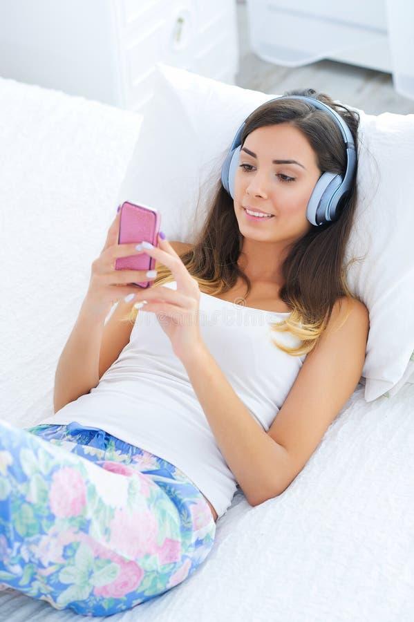 Bella giovane donna in cuffie che ascolta la musica immagine stock libera da diritti