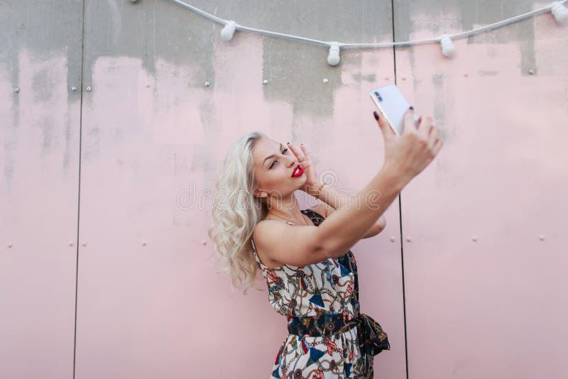 Bella giovane donna dei pantaloni a vita bassa in vestito alla moda che fa selfie fotografia stock